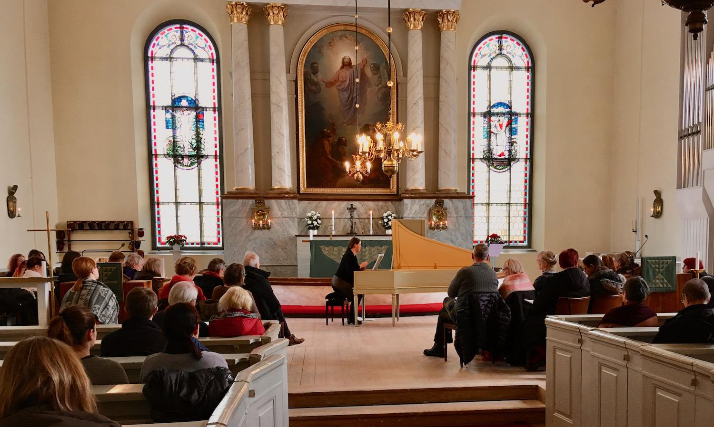 Anna-Maaria Oramo soittaa Oulun tuomiokirkon alttarin edessä cembaloa ja yleisö kuuntelee ympärillä