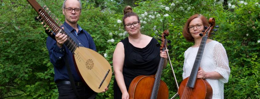 kolme soittajaa seisoo pensaikon edessä soittimiensa kanssa